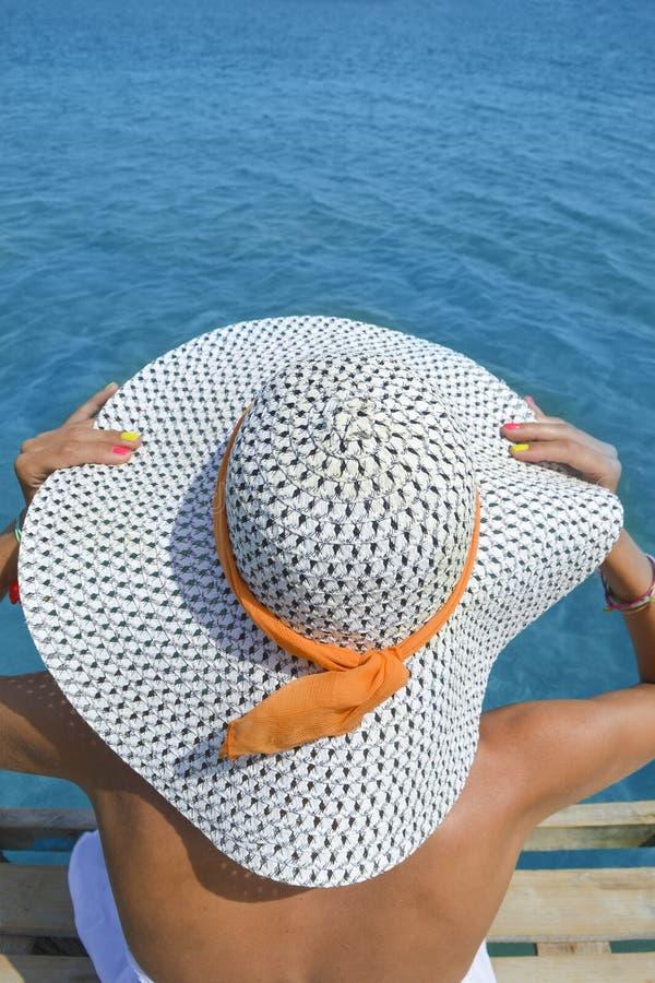 Jonge vrouw die het overzees van een dok bekijken De vakantie van de zomer stock foto's