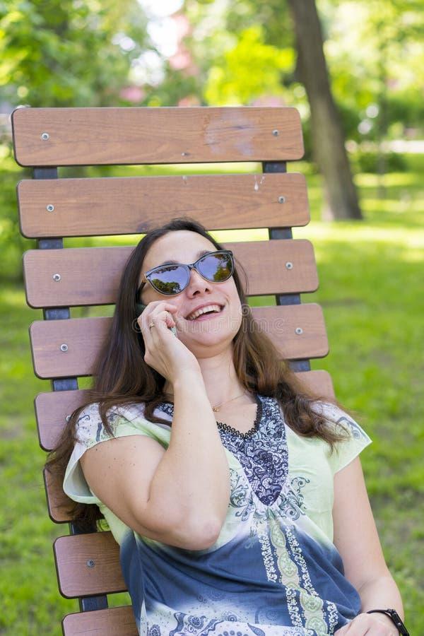 Jonge vrouw die in het park op de bank rusten Het mooie vrouwelijke ontspannen op een parkbank en het gebruiken van een smartphon stock afbeelding