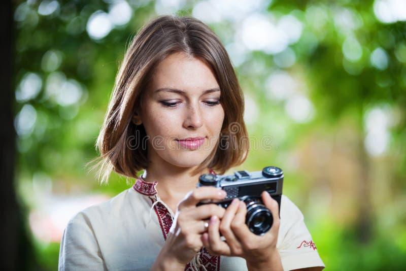 Jonge vrouw die het scherm van retro camera bekijken royalty-vrije stock foto