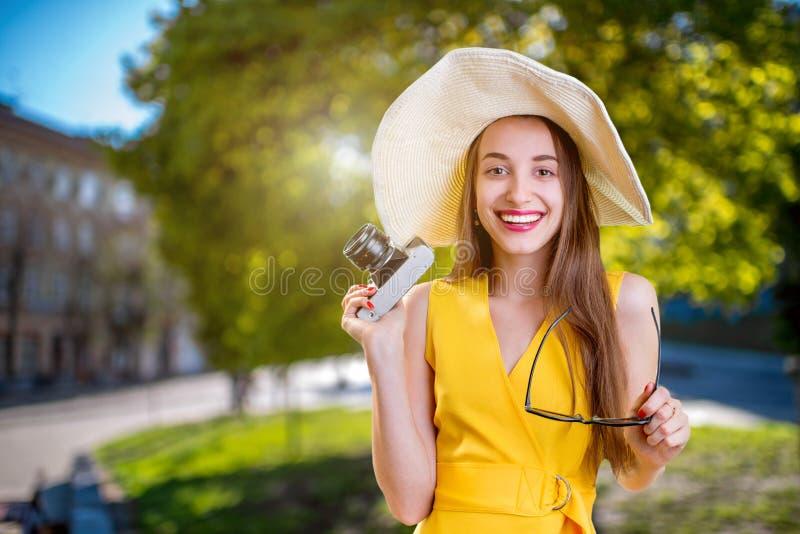 Jonge vrouw die in het stadspark reizen met camera gekleed in ye royalty-vrije stock afbeeldingen