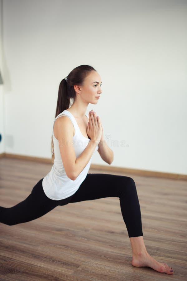 Jonge vrouw die het witte mouwloos onderhemd uitwerken dragen, die yogaoefening doen stock foto's
