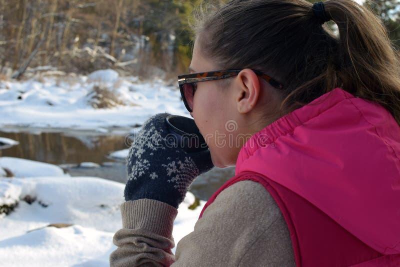Jonge vrouw die hete thee op de winterbos drinken stock afbeelding