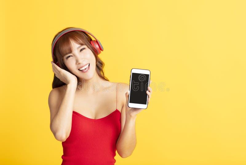 Jonge vrouw die in hoofdtelefoons aan muziek luistert stock foto's