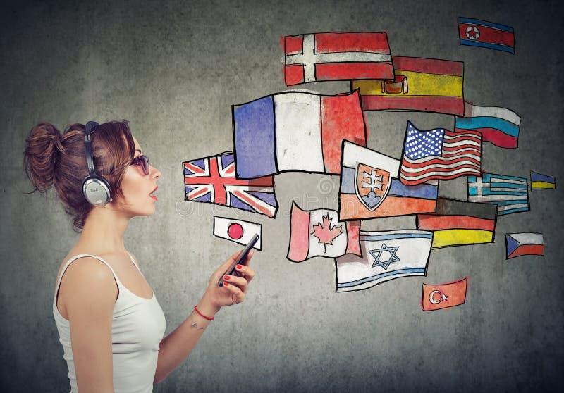 Jonge vrouw die in hoofdtelefoons verschillende talen leren stock foto's
