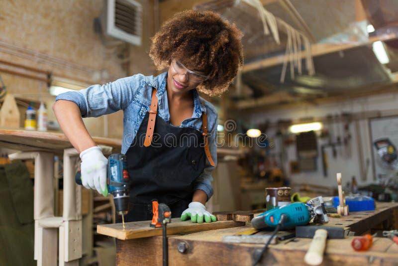Jonge vrouw die houtbewerking in een workshop doen stock fotografie