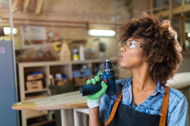 Jonge vrouw die houtbewerking in een workshop doen stock foto's