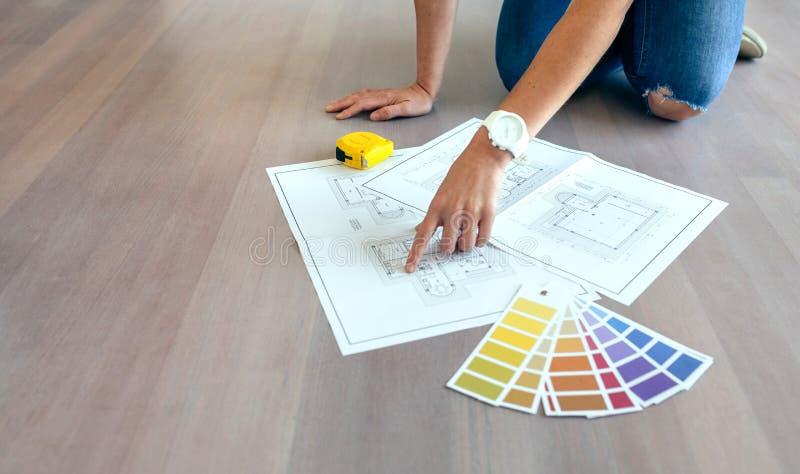 Jonge vrouw die huisplannen kijken stock afbeeldingen