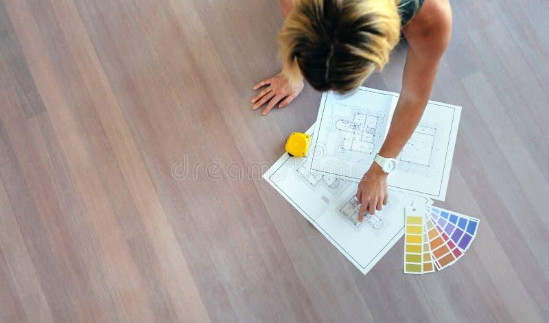 Jonge vrouw die huisplannen kijken stock foto's