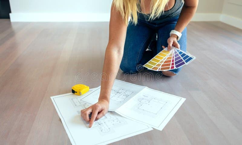Jonge vrouw die huisplannen kijken royalty-vrije stock foto