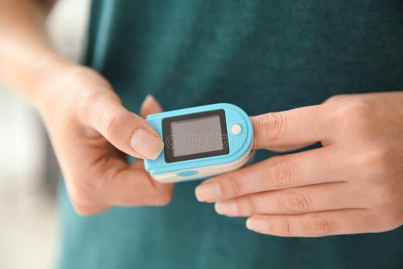 Jonge vrouw die impuls met bloeddrukmonitor controleren op vinger stock foto's