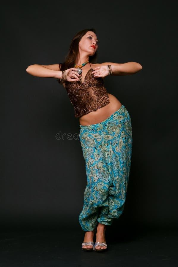 Jonge vrouw die in Indische kleren danst stock foto's