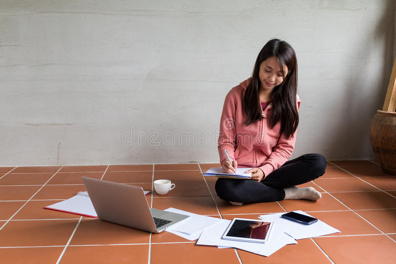 Jonge Vrouw die informatie thuis noteren stock afbeelding