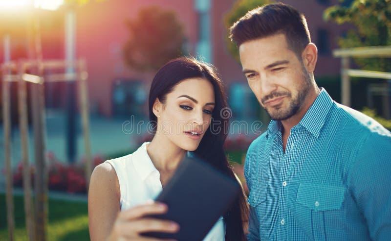 Jonge vrouw die interessant nieuws op tablet tonen aan de mens stock afbeeldingen