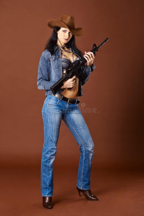 Jonge vrouw die in jeans een geweer houdt stock afbeeldingen