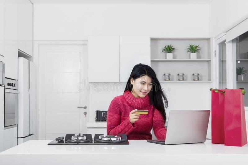 Jonge vrouw die kaartkrediet en laptop met behulp van royalty-vrije stock afbeelding