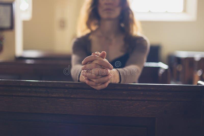 Jonge vrouw die in kerk bidden stock afbeeldingen