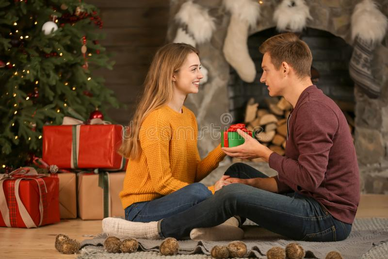 Jonge vrouw die Kerstmisgift van haar vriend thuis ontvangen royalty-vrije stock afbeeldingen