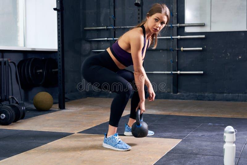 Jonge vrouw die kettlebell in gymnastiek opheffen royalty-vrije stock foto