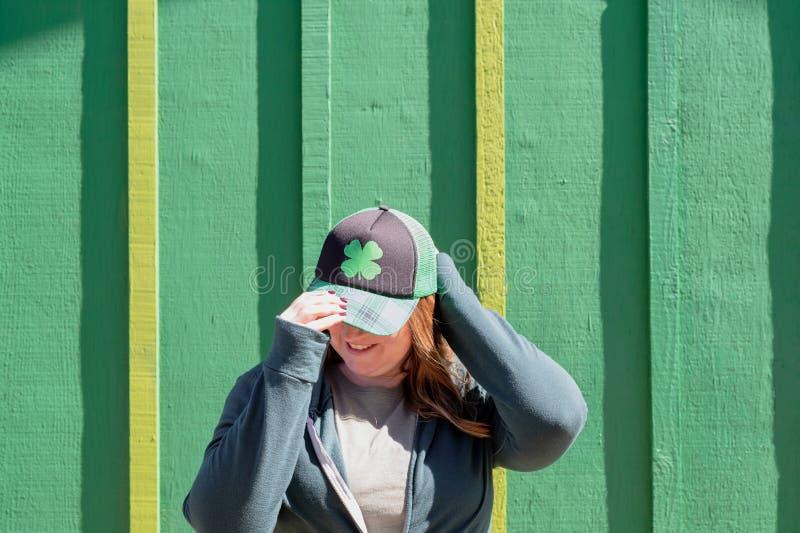 Jonge vrouw die klaverhoed dragen die zich voor groene muur bevinden stock foto