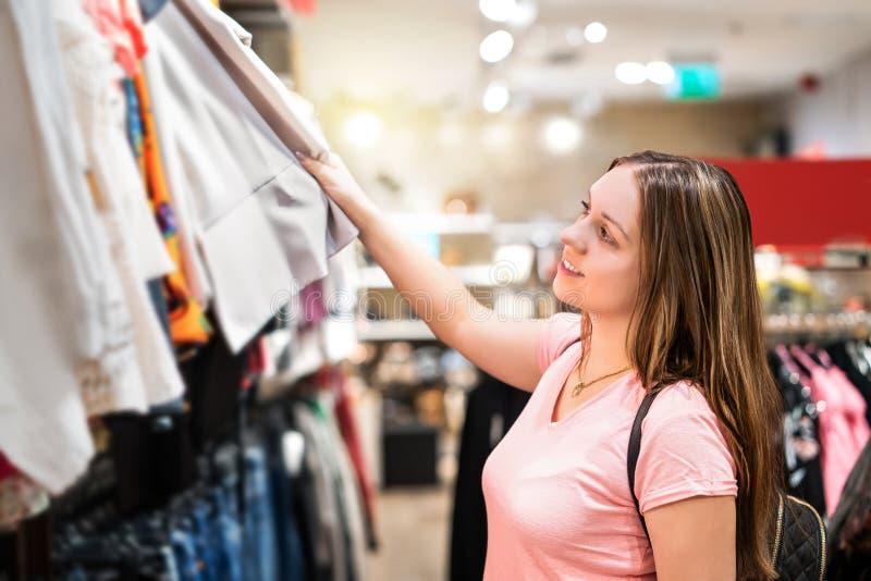 Jonge vrouw die in kledingsopslag winkelen stock afbeeldingen