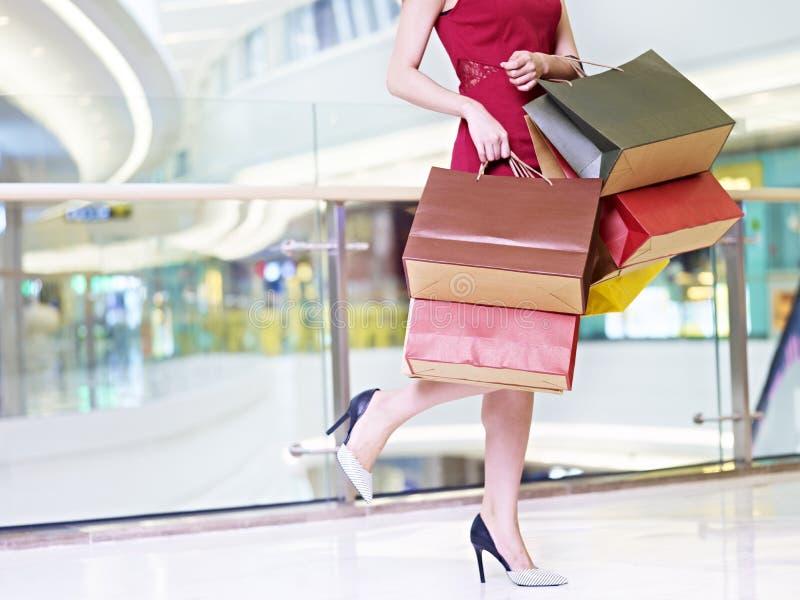 Jonge vrouw die kleurrijke document zakken dragen die in het winkelen mal lopen royalty-vrije stock afbeeldingen