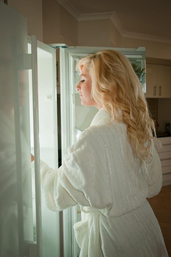 Jonge vrouw die in koelkast kijkt stock afbeelding