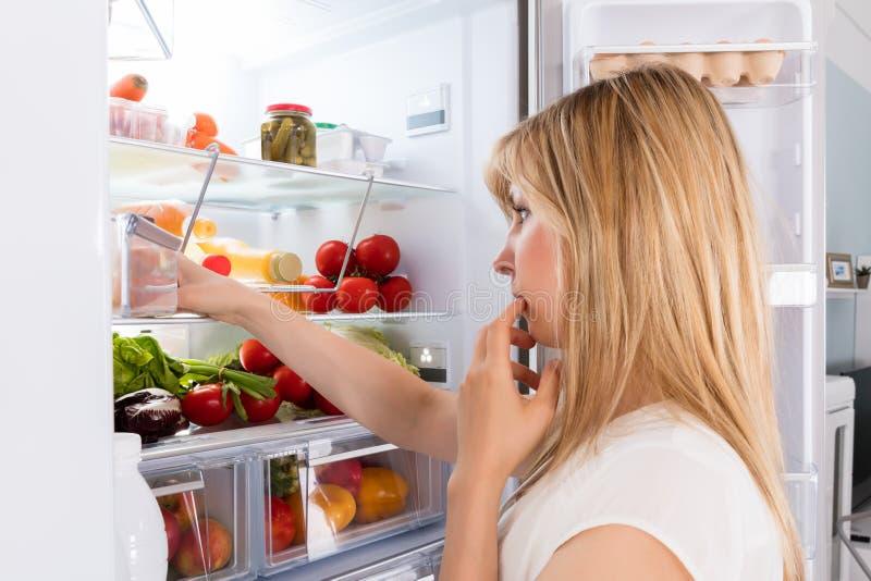 Jonge vrouw die in koelkast kijkt stock foto