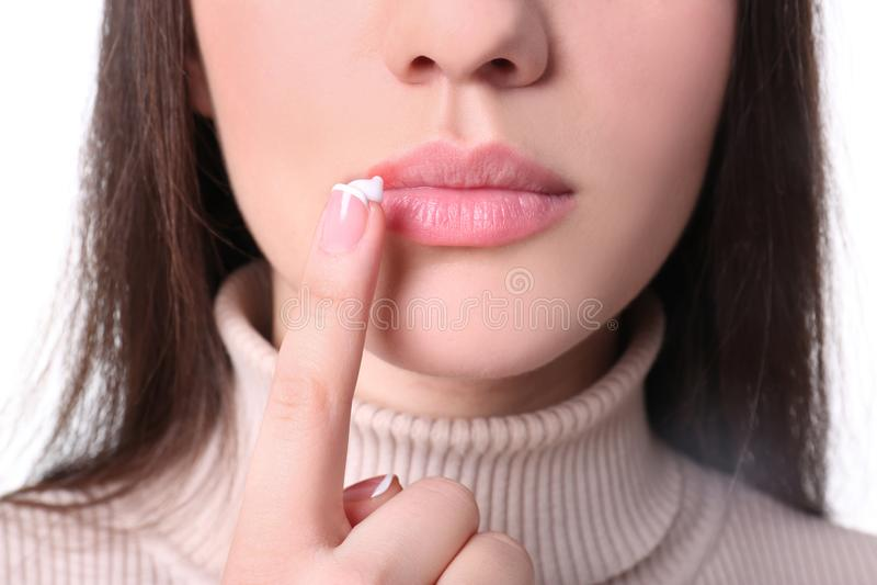 Jonge vrouw die koortsblaasjeroom op lippen toepassen stock afbeelding