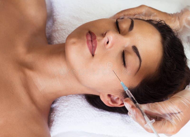 Jonge vrouw die kosmetische injectie ontvangen royalty-vrije stock afbeelding