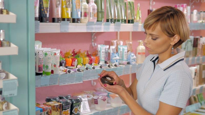 Jonge vrouw die kosmetische room in schoonheidswinkel kiezen royalty-vrije stock foto's