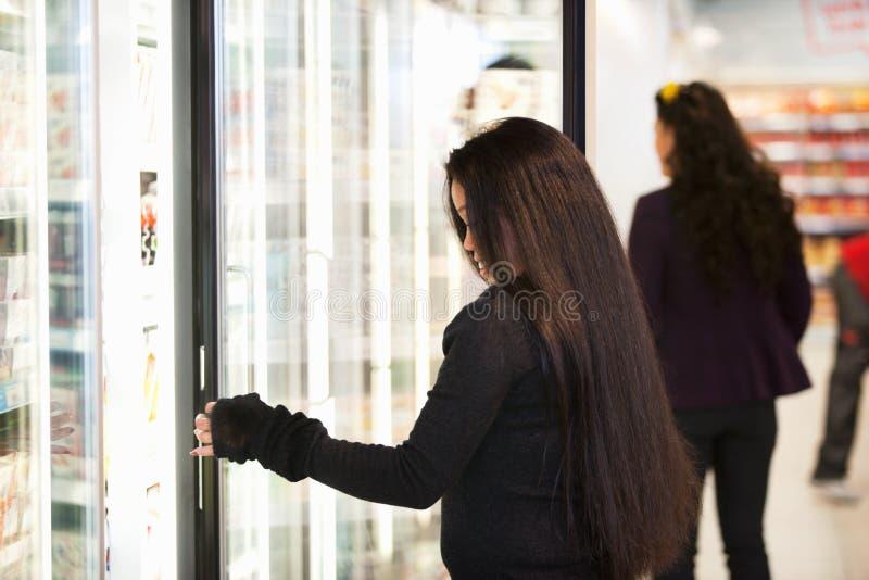 Jonge Vrouw die Koude Goederen koopt royalty-vrije stock afbeeldingen
