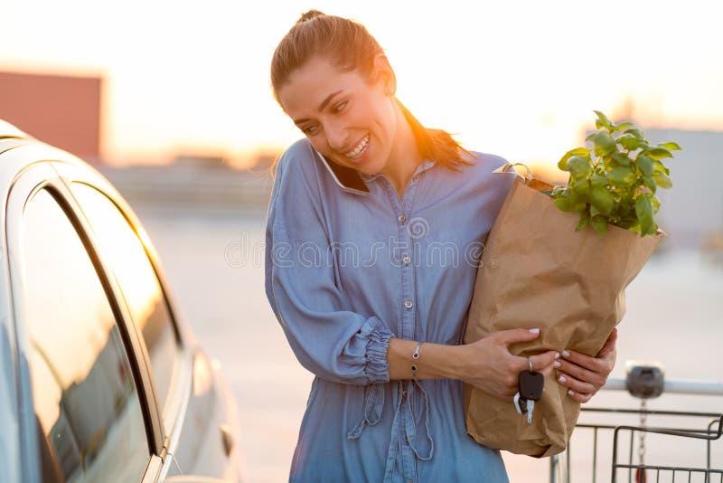Jonge vrouw die kruidenierswinkels zetten bij de autoboomstam royalty-vrije stock afbeeldingen