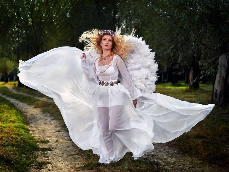 Jonge vrouw die lange witte kleding en engelenvleugels dragen stock afbeelding