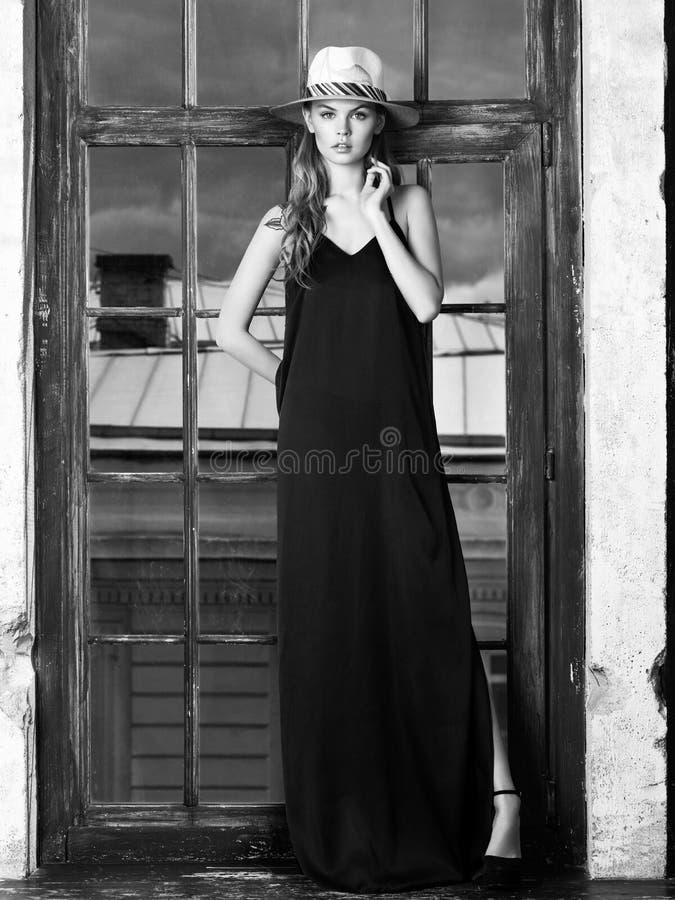 Jonge vrouw die lange zwarte kleding en hoed dragen royalty-vrije stock afbeelding