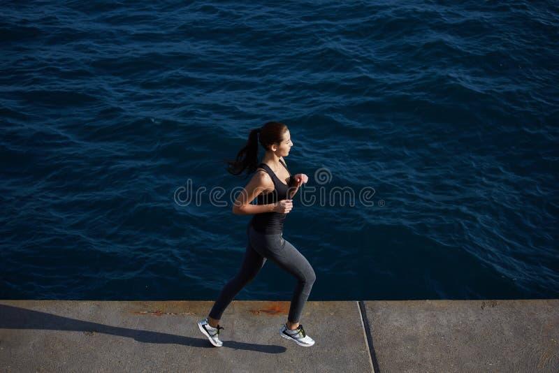 jonge vrouw die langs het strand met verbazende grote oceaangolven op achtergrond lopen royalty-vrije stock afbeelding