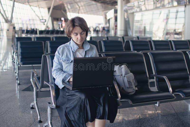 Jonge vrouw die laptop computer met behulp van bij luchthaven royalty-vrije stock fotografie
