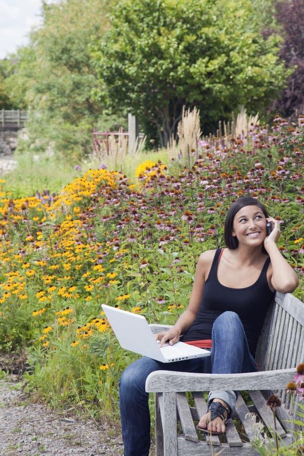 Jonge Vrouw die Laptop en Cellphone in Park gebruikt stock afbeelding