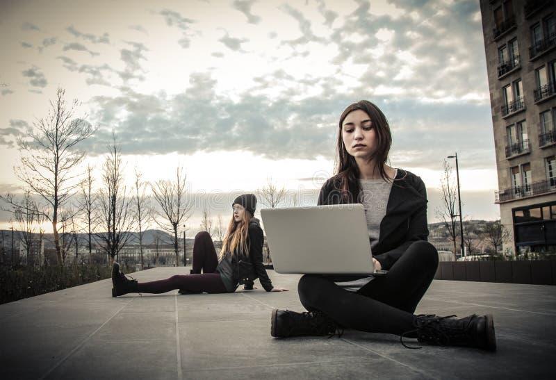 Jonge vrouw die laptop en de andere zitting in de tuin bekijken stock afbeeldingen