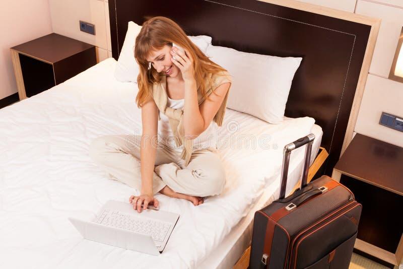 Jonge vrouw die laptop in hotel met behulp van royalty-vrije stock afbeelding