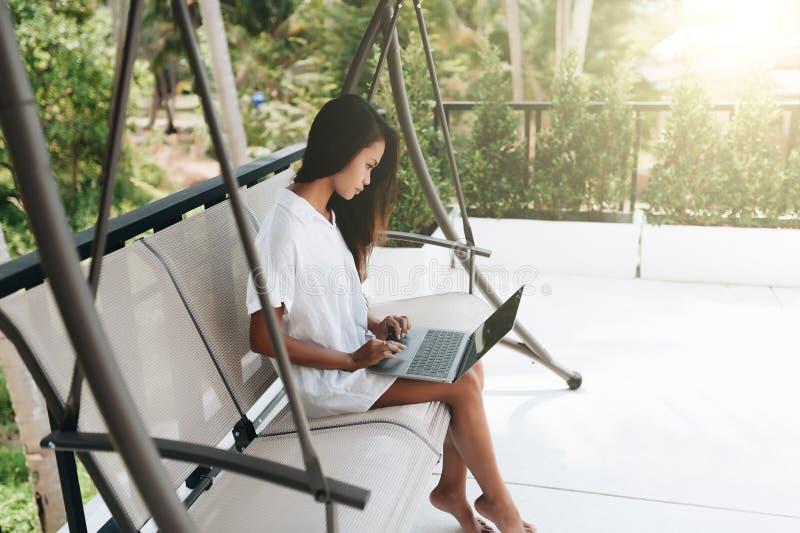 Jonge vrouw die laptop in openlucht met behulp van royalty-vrije stock fotografie