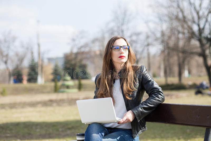 Jonge vrouw die laptop zitting op de bank gebruiken stock afbeelding