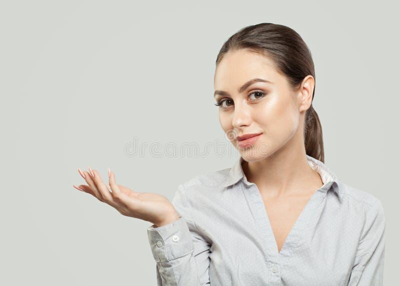 Jonge vrouw die lege exemplaarruimte op de open hand op witte achtergrond tonen Product Plaatsing en Reclame Marketing Concept stock foto