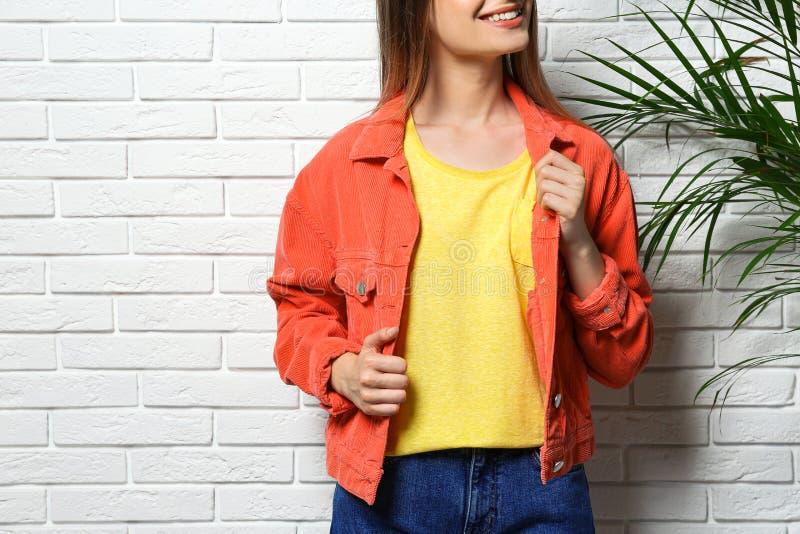 Jonge vrouw die lege t-shirt dragen dichtbij witte bakstenen muur Model voor ontwerp royalty-vrije stock afbeelding