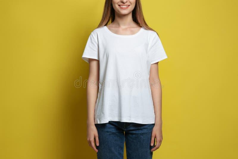 Jonge vrouw die lege t-shirt op gele achtergrond dragen Model voor ontwerp royalty-vrije stock fotografie