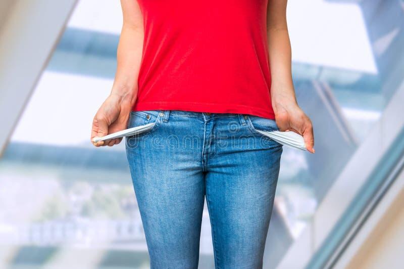 Jonge vrouw die lege zakken terugtrekken stock afbeeldingen
