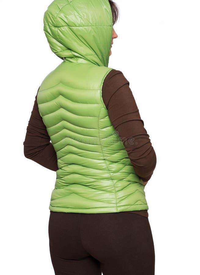 Jonge vrouw die lichtgroen packable benedenkogelvisvest dragen met een kap royalty-vrije stock afbeeldingen