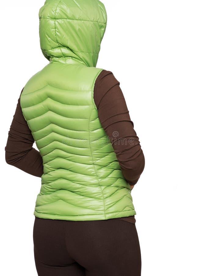 Jonge vrouw die lichtgroen packable benedenkogelvisvest dragen met een kap stock foto