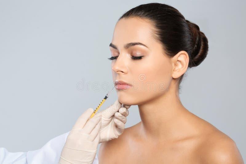 Jonge vrouw die lippeninjectie op grijze achtergrond krijgen royalty-vrije stock fotografie