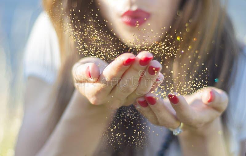 Jonge vrouw die magisch stofgoud van haar hand blazen stock foto's