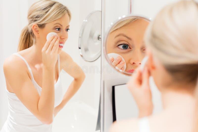 Jonge vrouw die make-up in badkamers verwijderen stock afbeelding